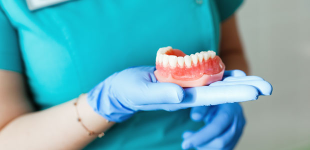 Hygienist holding set of dentures